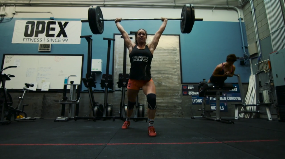 woman lifting weights over her head at crossfit