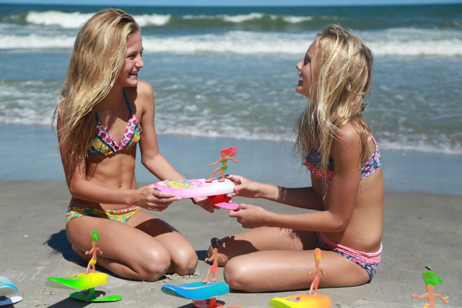 Two girls at the beach playing with toys